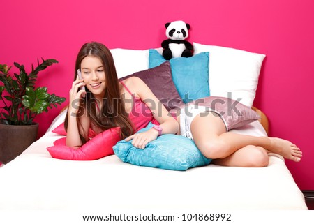 natural young woman making a call in her pink room - stock photo