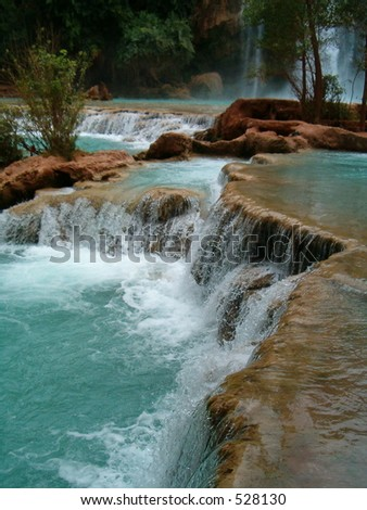 Naturally formed pools at waterfall base - stock photo
