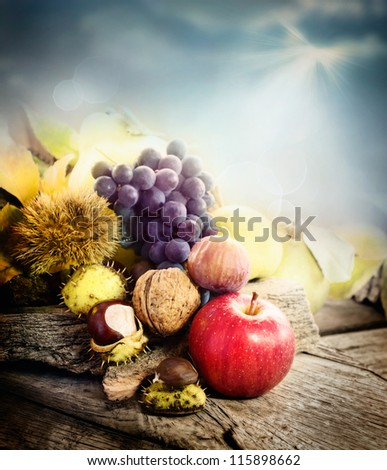 Nature background made of autumn fruit: chestnut, grapes, apple, walnut, pear, fig and quince. Fall season concept - stock photo