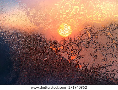 Nature background with ice pattern, bright sunlight and water drops on winter window glass - stock photo