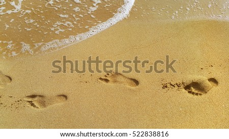 Nature background with sea water and footprints in the sand at the beach