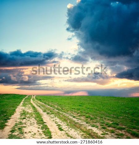Nature design. Field road in pure nature with blue sky and storm clouds - stock photo