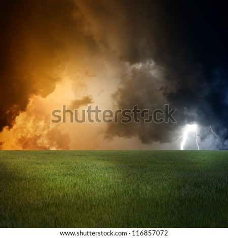 Nature force background - landscape with green field, dark sky and lightning - stock photo