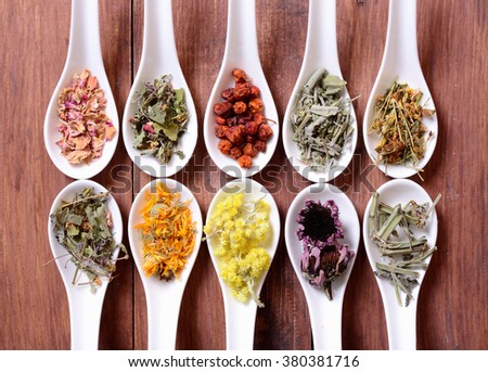 Nature medicine . Herbs in ceramic bowls on wooden background . - stock photo