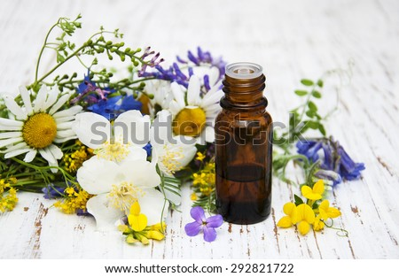 Nature oil with wildflowers on a old wooden background - stock photo