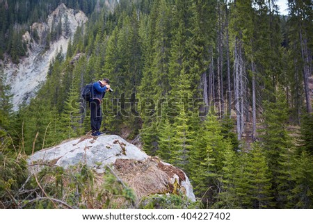 Nature photographer shooting a landscape with mountains and pine trees - stock photo