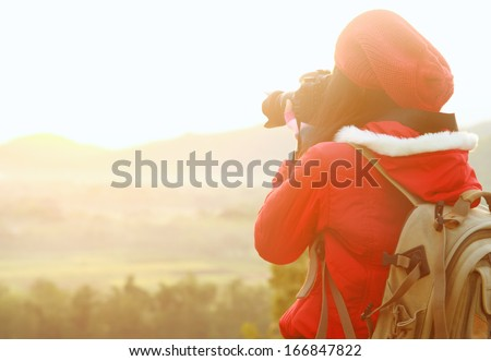 Nature photographer taking pictures during hiking trip - stock photo