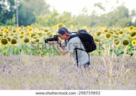 Nature photographer tourist with rucksack and cap  at work with new generation reflex camera inside a colored field with sunflower and lavender flowers. - stock photo