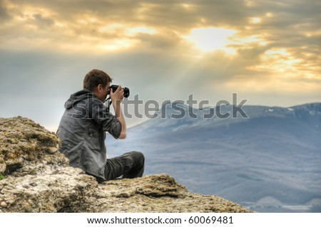 Nature photographer with digital camera on top of the mountain. HDR. - stock photo