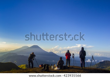 nature photographers in action during sunrise on prau mount central java indonesia - stock photo