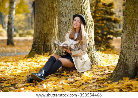 Nature quality time. Cheerful teenage girl smiling cheerfully holding a book resting near a tree in the forest  - stock photo