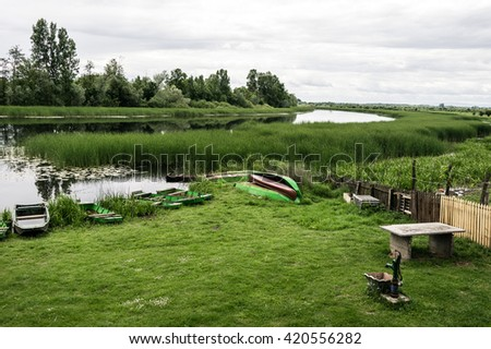 Nature reserve. Bulrush and sprig trees reflecting in a lake. Beautiful Lotos. Several small boats. Untouched Nature. Old small Draw Well. - stock photo