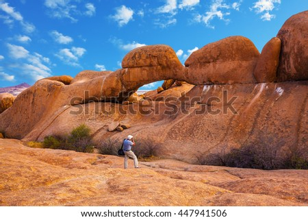 Nature reserve Spitzkoppe in Namibia. Picturesque stone arches are painted by iron oxides in red-orange color. Photographer enthusiastically takes the magical landscape