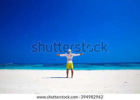 Nature. Seashore. Happy free Man Raising His Hands or Open arms enjoying life on tropical freedom beach. Success. Enjoyment.  - stock photo