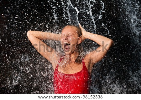 Nature spa concept - Young and emotional girl in red tank-top enjoying jungle waterfall