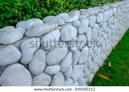 nature stone wall and green field - stock photo