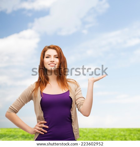 nature, summer, advertising and people concept - smiling teenage girl in casual clothes holding something on her palm over blue sky and grass background - stock photo