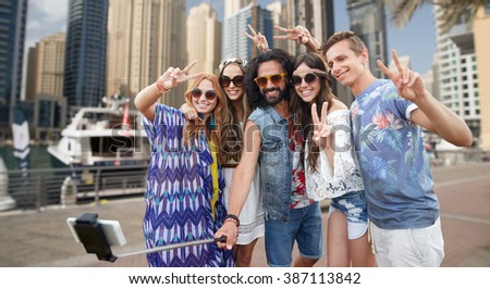 nature, summer, youth culture, technology and people concept - smiling hippie friends in sunglasses taking picture by smartphone on selfie stick and showing peace gesture over dubai city harbour  - stock photo