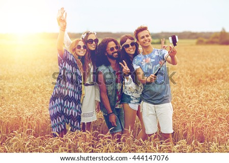 nature, summer, youth culture, technology and people concept - smiling young hippie friends in sunglasses taking picture by smartphone on selfie stick and showing peace gesture on cereal field - stock photo