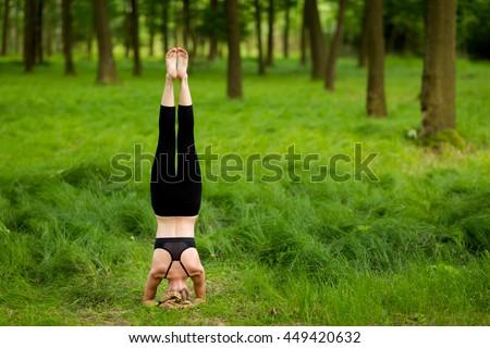Nature yoga session in beautiful green polish woods, between trees. Salamba Sirsasana - supported headstand - stock photo