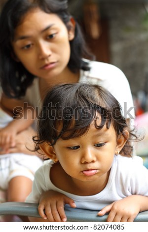 naughty asian ethnic little girl being advised by mom - stock photo