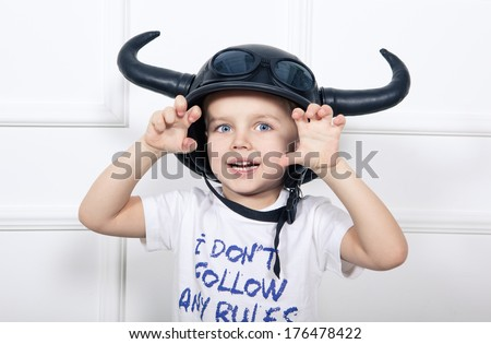 Naughty boy in black helmet with horns frighten the viewer - stock photo