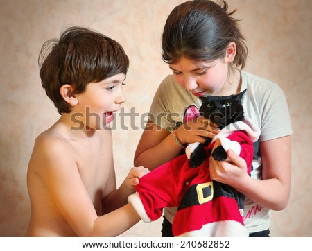 naughty brother and sister dress their black cat in santa costume - stock photo