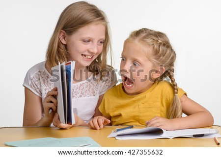 Naughty girls have fun on the lesson. Teenager is laughing about funny face that younger kid had made. Stationery for pupils and students on the wooden desk. - stock photo