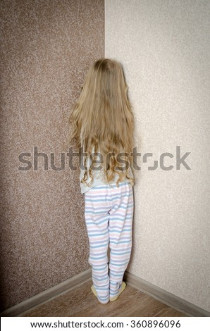 Naughty little girl is standing in the corner punished - stock photo