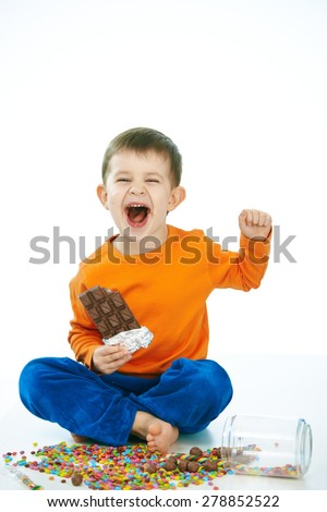 Naughty little kid eating chocolate sitting cross-legged on floor, sweets spilt. Laughing, hand in hair, isolated on white. - stock photo