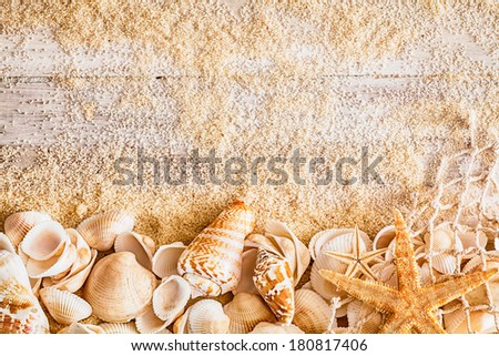 Nautical background and border of a collection of different seashells, a starfish and fishing net on rustic wooden boards with scattered sea sand , a nostalgic reminder of a happy summer vacation - stock photo