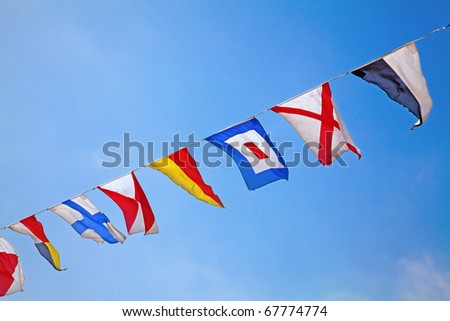Nautical flags against blue sky - stock photo