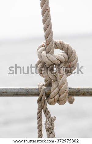 Nautical rope knot on a vintage sailboat at sea. Maritime background with copy space. Neutral colors - stock photo