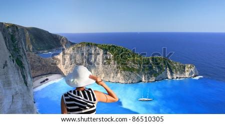 Navagio beach with woman on cliff, Zakynthos, Greece - stock photo