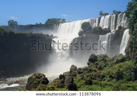 navigating in a boat to reach some iguazu falls - stock photo