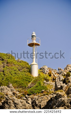 Navigation lighthouse on the rocks - stock photo