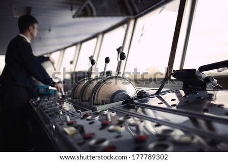 Navigation officer driving the ship on the river. Color corrected in film tones - stock photo