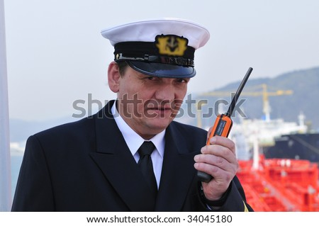 Navigation officer is talking by VHF radio, looking ahead on the navigation bridge of ocean ship - stock photo