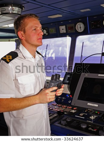 Navigation officer manages devices, looking ahead on the navigation bridge of ocean ship - stock photo