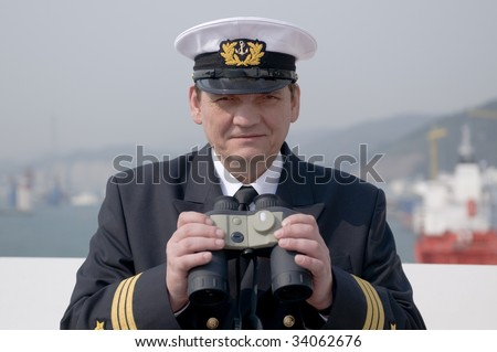 Navigation officer with binocular, looking ahead on the navigation bridge of ocean ship - stock photo