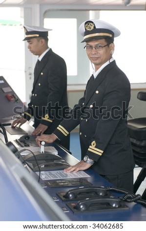Navigation officers manage devices, looking ahead on the navigation bridge of ocean ship - stock photo
