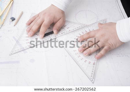 navigator is measuring with triangles on a mercator map - stock photo