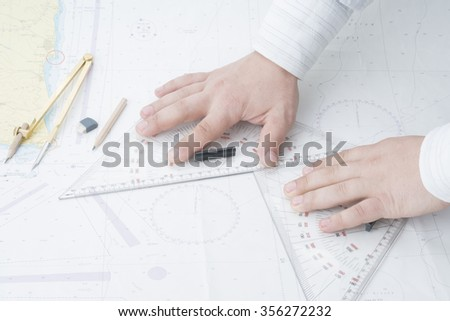 navigator measure by 2 triangles on navigation map - stock photo