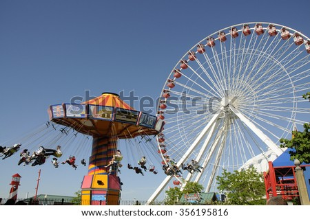 NAVY PIER AMUSEMENTS CHICAGO USA - CIRCA  2012 - Funfair rides on the Ferris Wheel and Wave Swinger on Navy Pier Chicago Illinois USA - stock photo