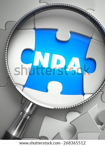 NDA - Word on the Place of Missing Puzzle Piece through Magnifier. Selective Focus. - stock photo
