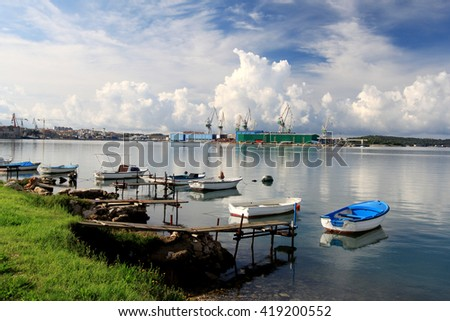 ndustrial Container Cargo freight ship with working crane bridge in shipyard at dusk for Logistic Import Export background - stock photo