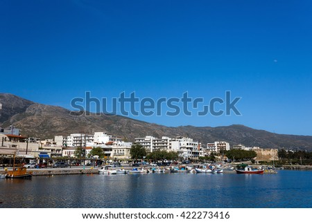 Nea Stira port with anchored fish boats against a blue sky and blue waters in Evia, Greece - stock photo