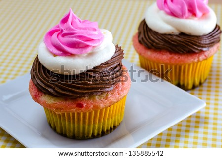 Neapolitan frosted cupcakes on white square plate with yellow gingham checked tablecloth