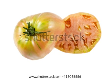 Near ripe ox heart tomato, Solanum lycopersicum, showing many small seed compartments, called locules, and a nice pink flesh. - stock photo