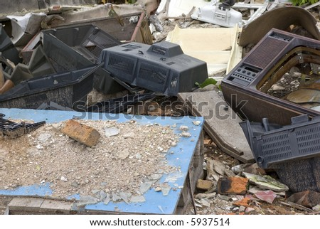 Near to ruins of the house. Old TVs, bricks, dust - stock photo